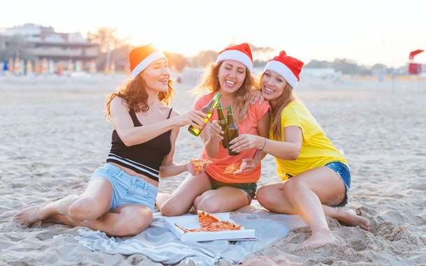 A group of friends cheers on the beach on a tropical Christmas vacation while wearing Santa hats and eating pizza.