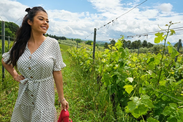 the woman is walking around the vineyard