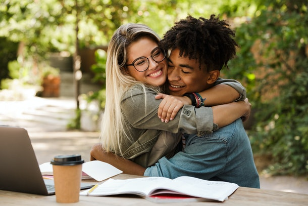 Joyful young multiethnic couple spending time together at the park, studying while sitting at the table with laptop, hugging