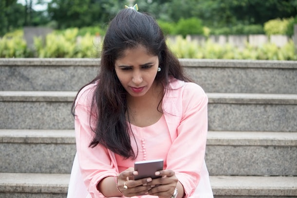 Worried young woman text messaging on mobile phone