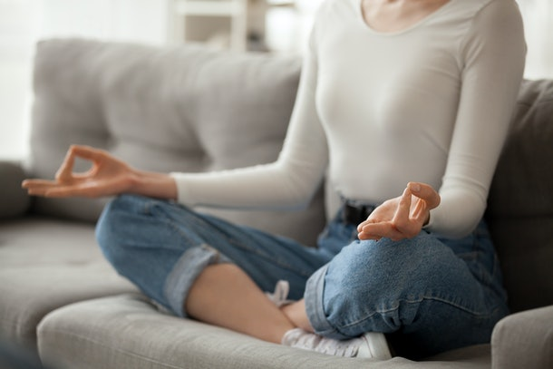Close up of focused female sit on cozy couch meditating with mudra hands, calm woman practice yoga in lotus position on sofa at home, girl manage stress controlling emotions. Healthy lifestyle concept