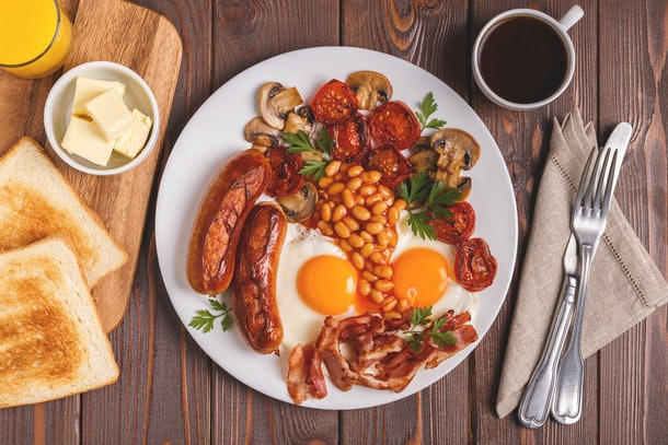 Traditional full English breakfast with fried eggs, sausages, beans, mushrooms, grilled tomatoes and bacon on wooden background. Top view