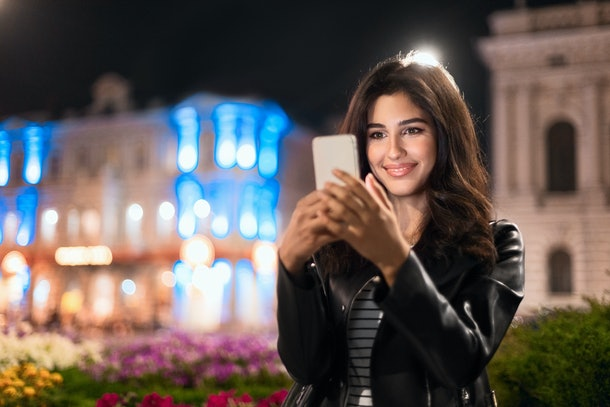 Happy girl texting on phone, walking at night in the city, copy space