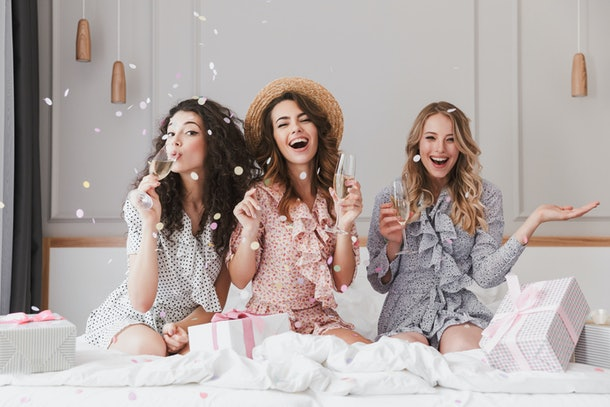 Image of caucasian stylish women 20s wearing dresses celebrating bachelorette party in fashion apartment with champagne and falling confetti