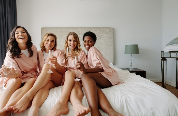 Bride and bridesmaids celebrating bachelorette party in bedroom. Happy females friends sitting on bed and having champagne.