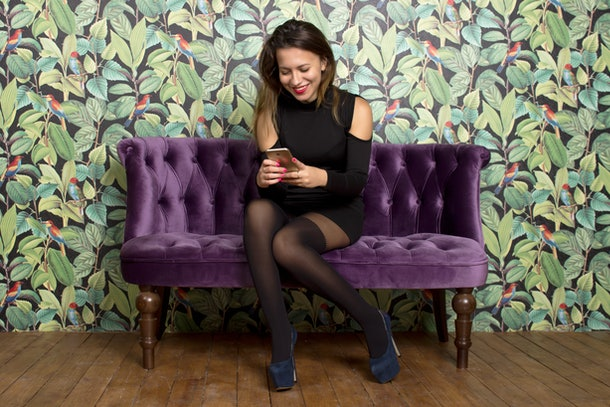 Smiling woman prepared to party  with phone on the purple sofa