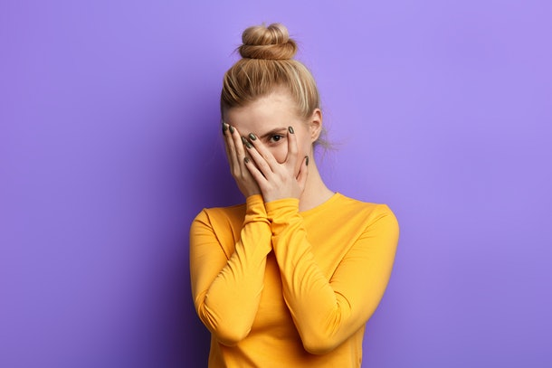 Stressed scared woman covering her face with palm, feeling afraid of stressful examination,beautiful stylish girl hiding herself behind palms.close up portrait. isolated blue background