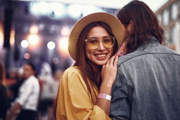 Portrait of charming young lady in hat standing close to hipster guy and looking at camera with smile