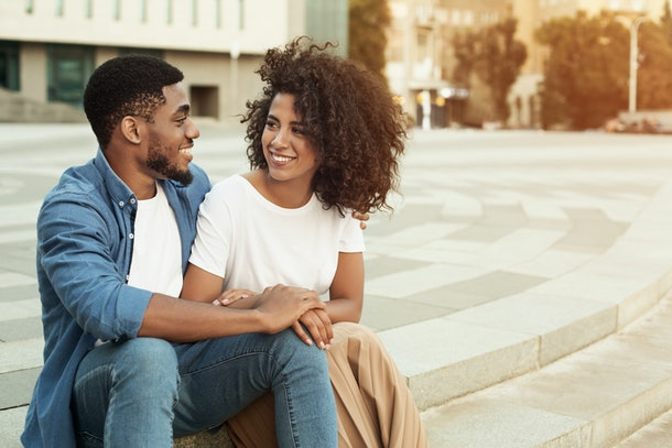 African-american couple talking, enjoying date, walking outdoors in city