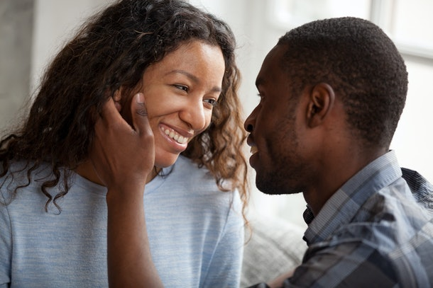 Happy African American couple having date at home, sitting together on couch, loving man touching attractive smiling woman face with tenderness, looking in eyes to each other, feelings, first kiss