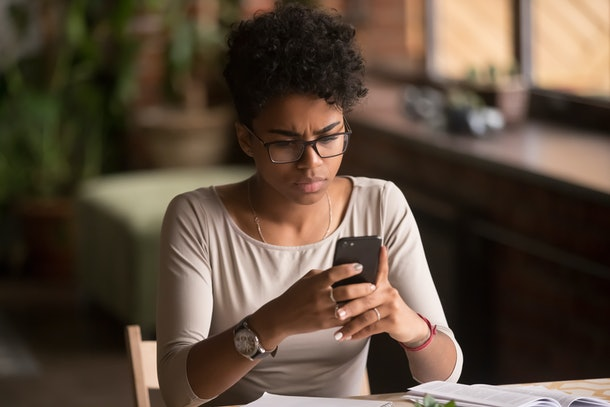 Upset confused african woman holding cellphone having problem with mobile phone, frustrated angry mixed race girl reading bad news in message looking at smartphone annoyed by spam or missed call