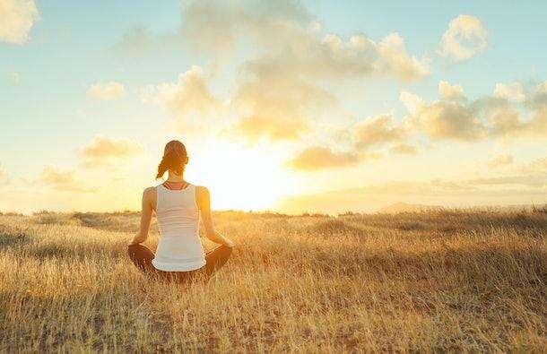 Woman meditating against a beautiful sunset. Mind body spirit.