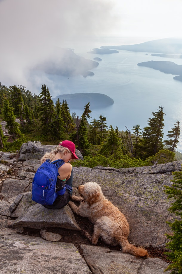 Adventurous Girl is hiking with a dog on top of Unnecessary Mountain during a sunny and cloudy summer day. Located in West Vancouver, British Columbia, Canada.