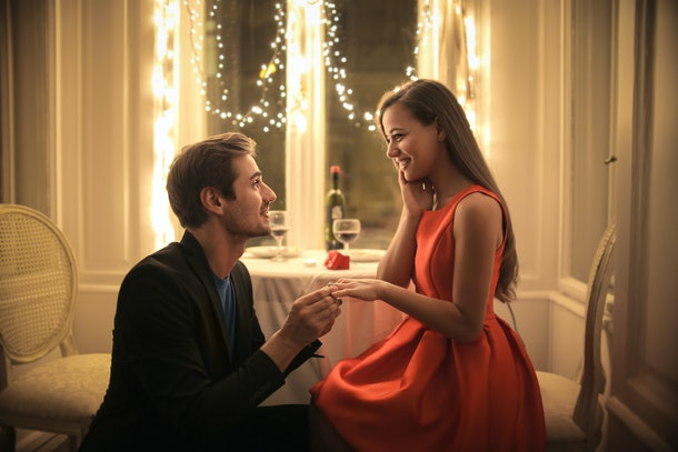 Handsome man proposing a beautiful woman to marry him in an elegant restaurant