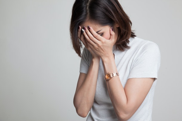 Sad young Asian  woman cry with palm to face on gray background