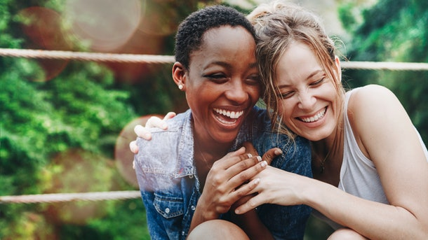 Cheerful girls embracing each other, showing each other they love them