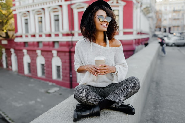 Street fashion look. Stylish black girl sitting on the bridge and holding cup of coffee or tea during her free time. Freelance woman. Wearing black hat and sunglasses.