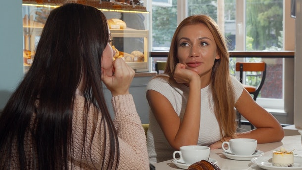 Attractive woman talking to her best friend at the coffee shop