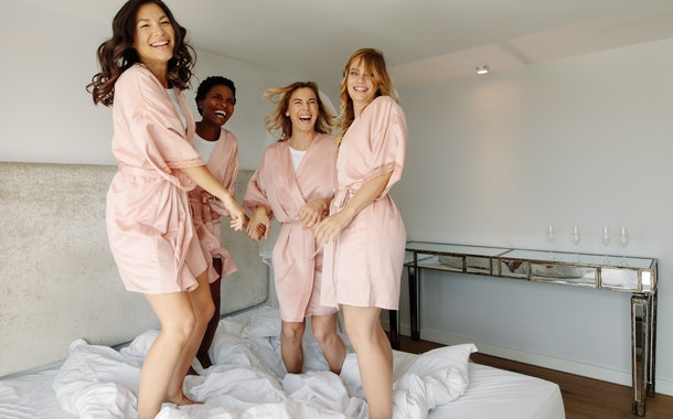 Bride and bridesmaids jumping on bed before wedding. Females having a great time at the hen-party, jumping on bed and smiling.