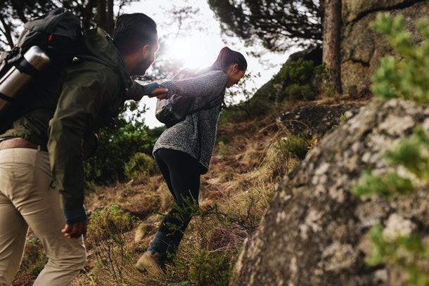 Female hiker helping her boyfriend uphill in the countryside. Young couple hiking in mountain.