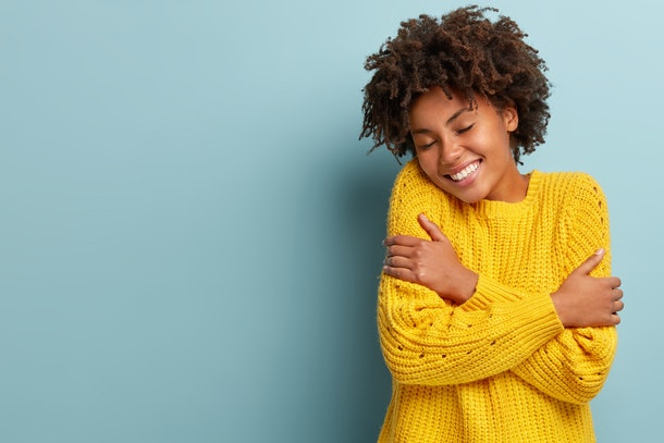 Happy young dark skinned woman hugs herself, feels warmth cozy, wears yellow knitted sweater, enjoys tenderness and comfort, smiles broadly, isolated over blue wall with blank space for your text