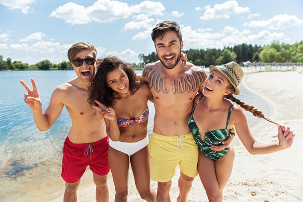 Happy group of four friends resting on summer beach