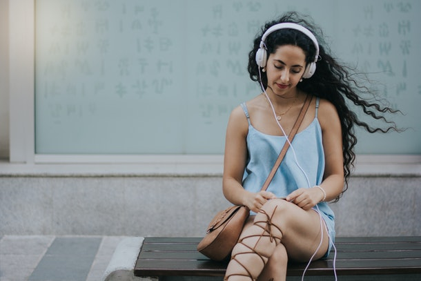 Woman texting on smartphone and listening to music in city