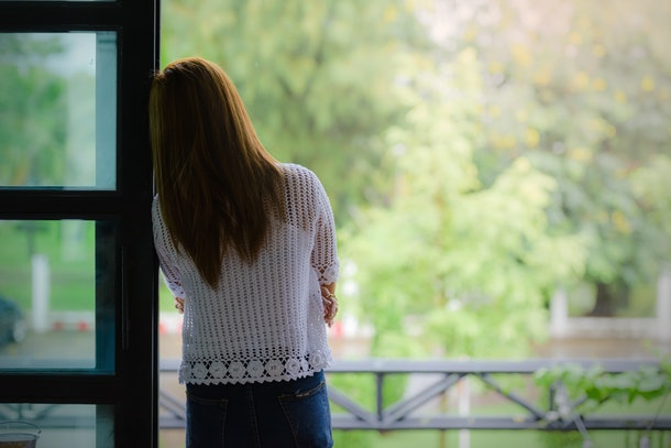 Depressed women. Asian beautiful girl standing at the window.