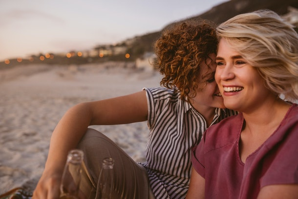 Laughing young lesbian couple talking and having drinks while sitting together on a sandy beach watching a romantic sunset