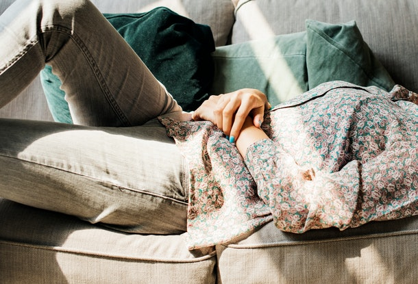 A woman with grey jeans and a printed top lies on her couch and rests in the sunlight.