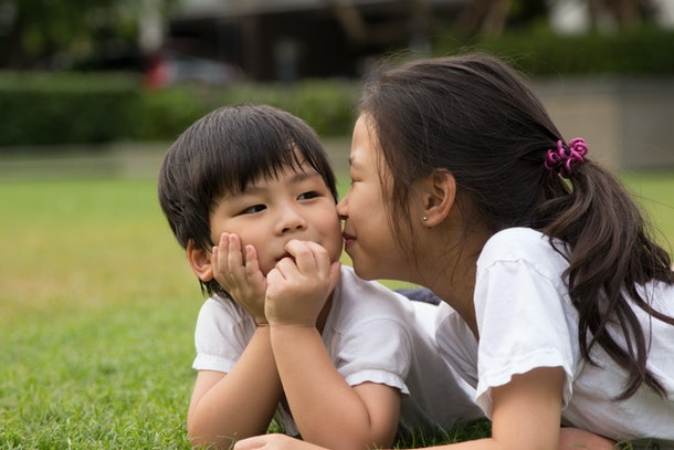 Sister wants to kiss her cute brother and the boy likes being kissed.