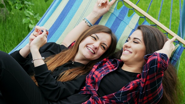 Lesbian girlfriends lie in hammock in garden. Two lesbians woman hug and laugh, lgbt concept