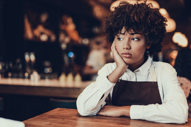Portrait of upset waitress. She looking aside and sitting behind table while touching cheek by palm hand