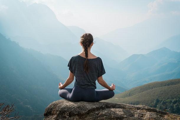Woman meditates in yoga asana Padmasana