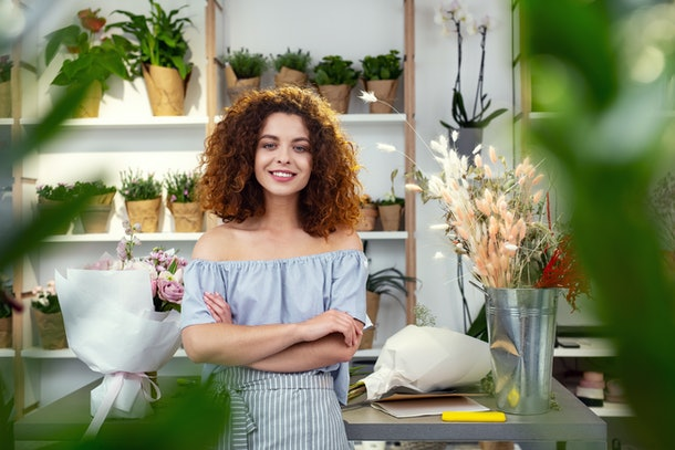Friendly smile. Joyful confident woman looking at you while standing cross handed in the flower shop