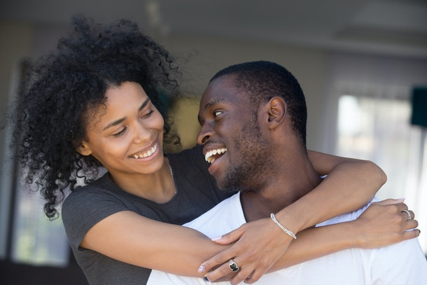 Portrait of happy black husband and wife embrace looking at each other, smiling African American couple cuddle having fun together, excited girlfriend hug boyfriend from behind, showing love and care