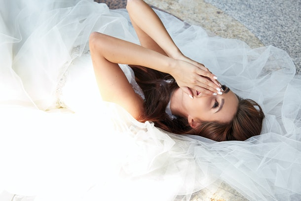 Beautiful tender young woman sexy brunette bride in a luxury white wedding dress laying on the marble floor in Castle style filing Summer happiness awaits the groom before the wedding ceremony