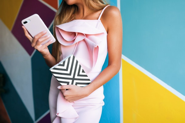 Glamorous woman in the pink dress with the phone and notebook standing near the colorful wall, blonde, makeup, style, texting messages