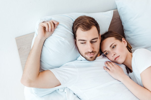 pensive couple in white t-shirts lying on bed and looking away