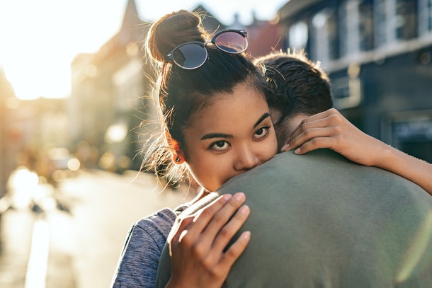 Young woman hugging her boyfriend while standing together on a city street in the late afternoon