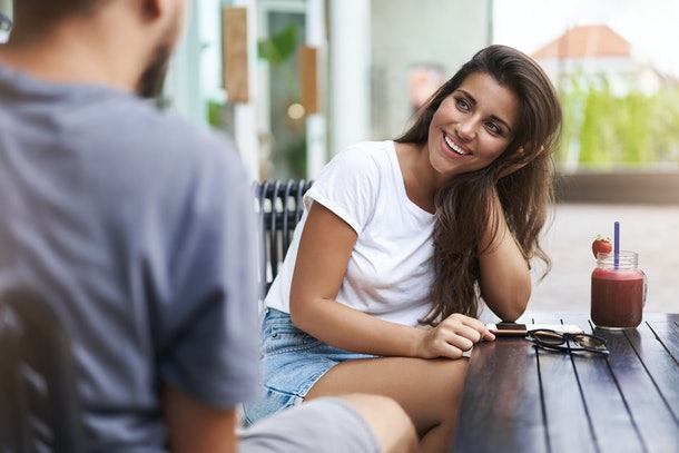 Couple sitting outdoor terrace cafe talking happily woman laughing flirty gaze camera touch hair coquettish giggling funny boyfriend story drink strawberry beverage, have conversation