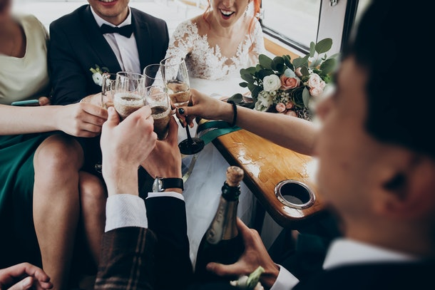 hands with glasses of champagne clinking, stylish happy bride and groom toasting laughing and having fun with bridesmaids and groomsmen inside car. emotional moment, space for text. wedding party