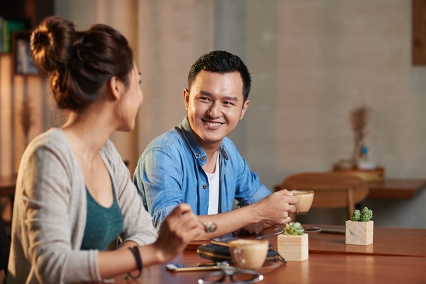 Portrait of young man and woman looking at each other and smiling, meeting in cafe for coffee