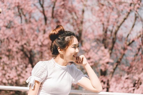 portrait of young asian woman with scenery of wild Himalayan cherry blossoms, trees, field and forest