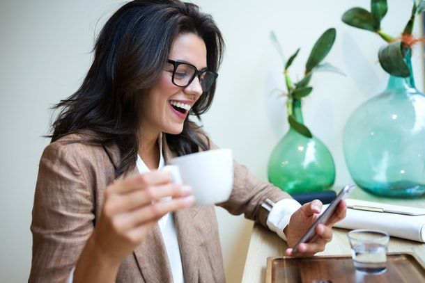 Shot of laughing young businesswoman texting with her mobile phone in the coffee shop.