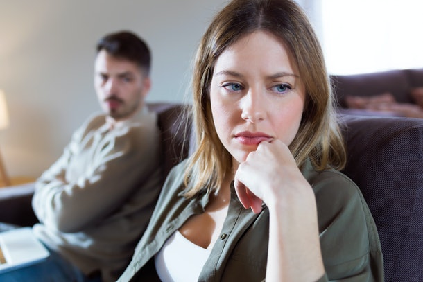 Portrait of offended young woman ignoring her angry partner sitting behind her on the couch at home.