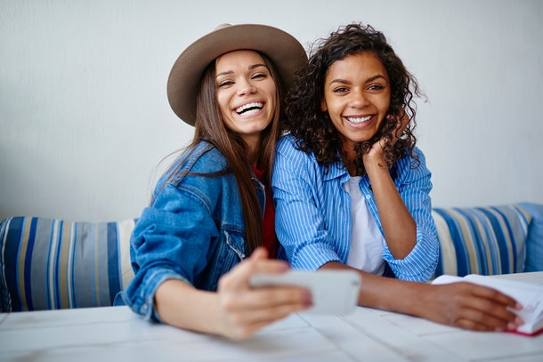Portrait for cheerful multiracial women posing for common selfie on smartphone during friendly meeting in cafe,hipster girls having fun together laughing making pictures using telephone camera