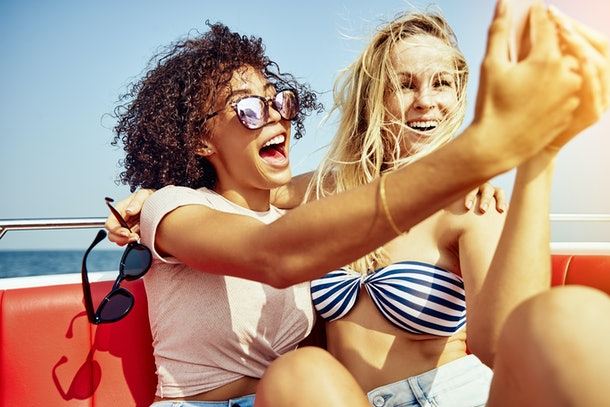 Two young female friends sitting together on a boat taking selfies together and laughing during their summer vacation