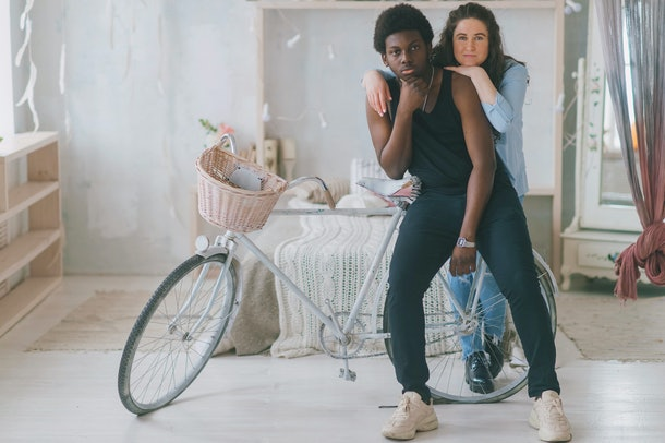Multicultural love and relationships concept. Loving and embracing interracial couple indoor vintage style portrait. Dark skinned man standing near bicycle with his cheerful happy white girlfriend