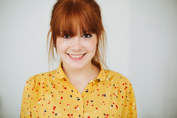 A cute redheaded girl with freckles smiles cheerful into the camera.